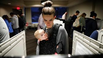 Kristen Leach votes with her six-month-old daughter, Nora, on election day in Atlanta, Tuesday, Nov. 6, 2018. (AP Photo/David Goldman)