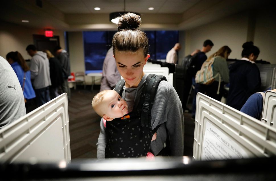 Kristen Leach votes with her six-month-old daughter, Nora, on election day in Atlanta, Tuesday, Nov. 6, 2018.