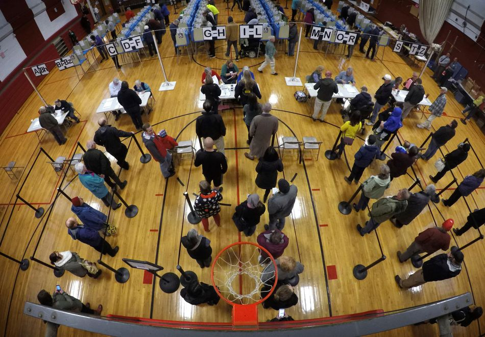 Voters wait in line in the gymnasium at Brunswick Junior High School to receive their ballots for the midterm election in Brunswick, Maine.