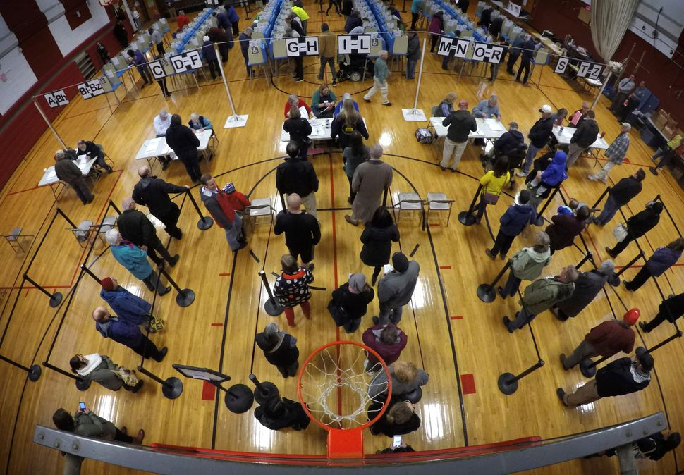 Voters wait in line in the gymnasium at Brunswick Junior High School to receive their ballots for the midterm election in Bru