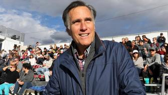 In this Friday, Nov. 2, 2018 photo, former GOP presidential nominee Mitt Romney watches the Lone Peak High School football game against Davis High School in Highland, Utah. Romney is stumping for fellow Republican candidates as he sails toward a likely victory Tuesday in the race for a U.S. Senate seat from Utah and an official return to public office. (AP Photo/Rick Bowmer)