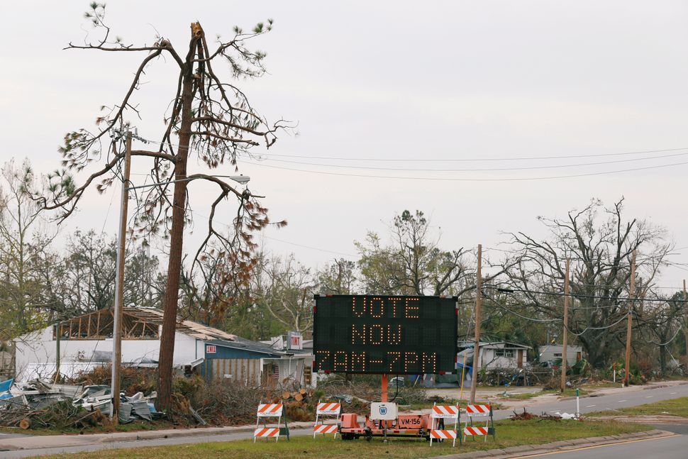 A sign directs voters to a new polling location where Hurricane Michael destroyed many schools and other buildings used as po