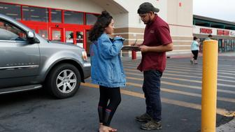 In this Aug. 15, 2018, photo, Jazmin Cortez, left, registers Victor Arias to vote in Las Vegas. Democrats in Nevada are working to register and engage Latino voters ahead of this year's midterms, hoping to recreate the big wins that the state's Hispanic and immigrant community are credited with delivering two years ago. (AP Photo/John Locher)