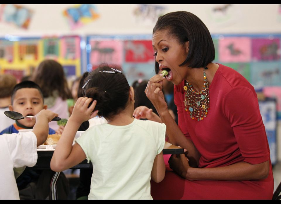 First lady Michelle Obama eats a piece of broccoli as she sits down to eat with students during their visit to New Hampshire