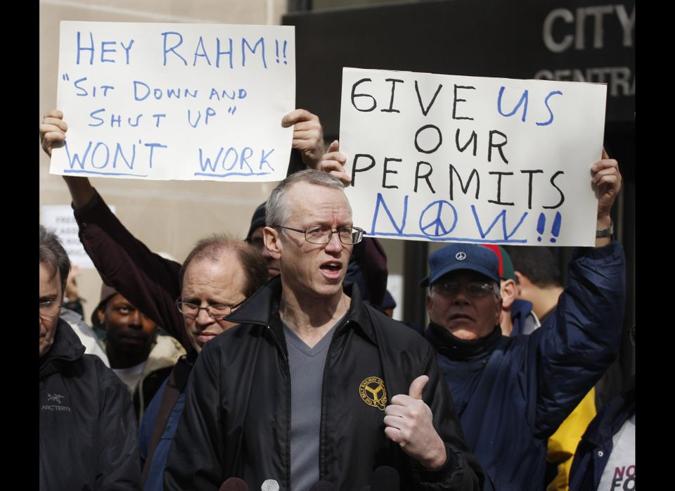 Andy Thayer, center, joins other activists outside the City of Chicago Central Hearing Facility Tuesday, March 27, 2012, in C