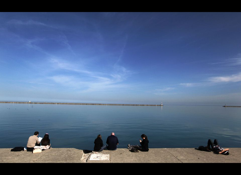 Small groups of people gather on the Lake Michigan waterfront at DuSable Harbor Tuesday, March 13, 2012, in Chicago. Temperat