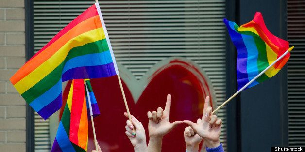 hands waving gay flags in front ...