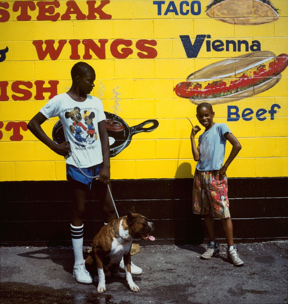Two boys with a dog stand outside a hot dog stand, 1987.