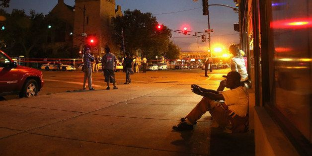CHICAGO, IL - AUGUST 19:  Neighborhood residents watch as Chicago police investigate a shooting in front of the Uptown Baptis