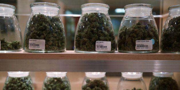 Jars containing various strands of medical marijuana sit behind a display case at the River Rock Medical Marijuana Center in
