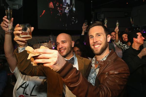 Fernando Mojica (L) and Drew Freeman raise a toast with other patrons at Sidetrack in celebration of the Illinois General Ass