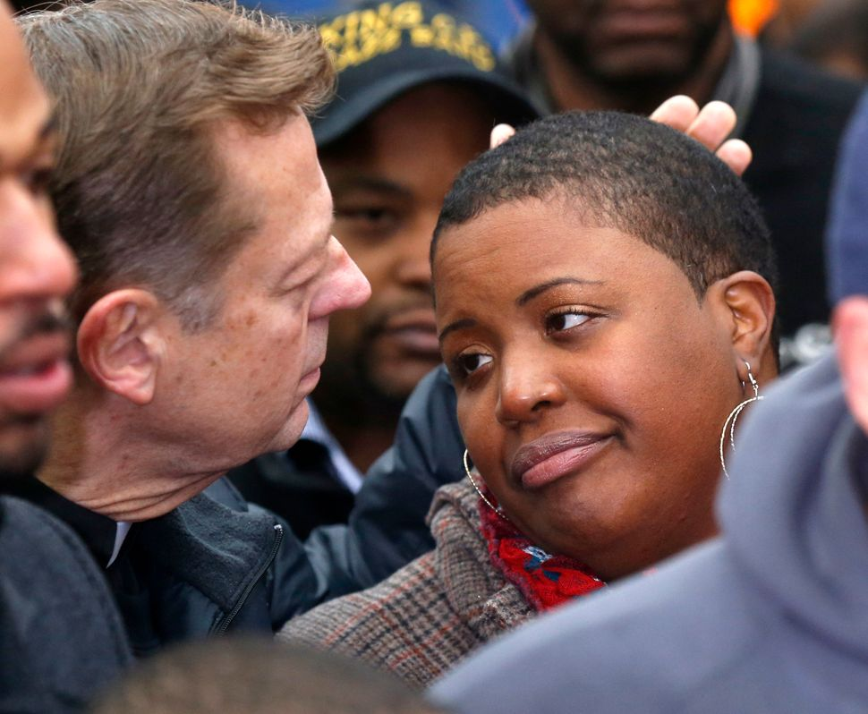Father Michael Pfleger , left, consoles Cleopatra Pendleton during a news conference seeking help from the public in solving
