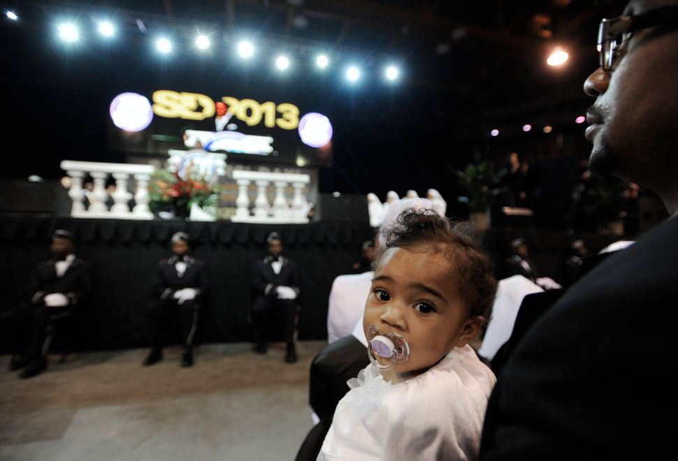 One-year-old Yasmina Rahman, of Atlanta, listens as the Minister Louis Farrakhan speaks during the Saviours' Day annual conve