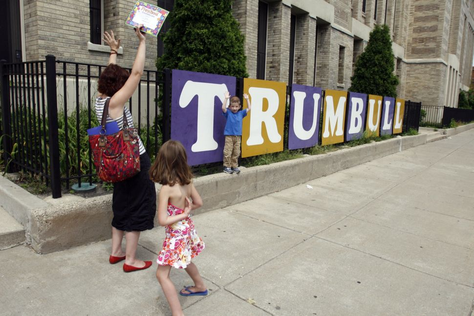 Lucy Riner prompts her son Luka Riner, 4, to raise his hands next to a sign outside at Trumbull Elementary School on the last