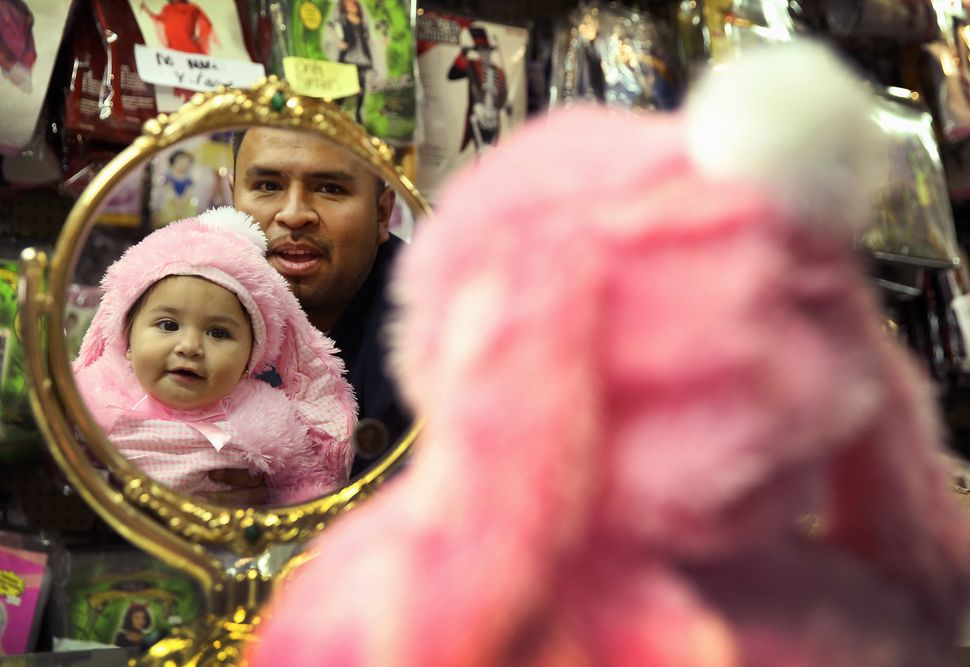 Tony Garcia lets his 11-month-old daughter Yaretzi Garcia see herself in a bunny Halloween costume at Fantasy Costumes on Oct