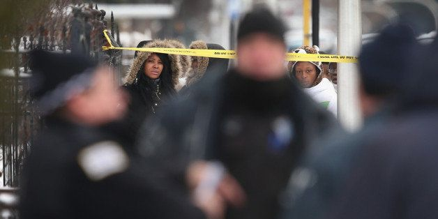 CHICAGO, IL - DECEMBER 15:  Neighborhood residents watch as police investigate a homicide scene after a 24-year-old man was f