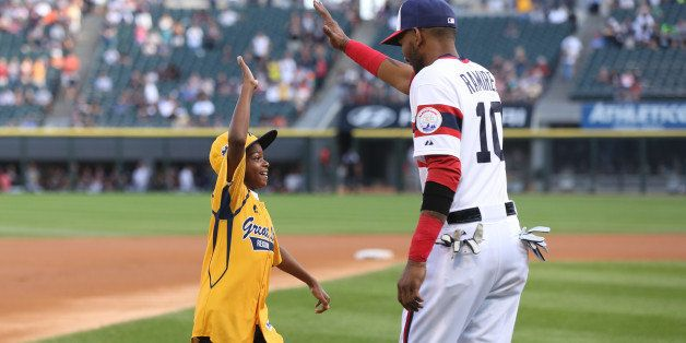 CHICAGO, IL - AUGUST 30: A member of the Jackie Robinson West Little League Team gets a high Five from Alexei Ramirez #10 of