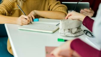 Hands of group of unrecognisable students doing homework.