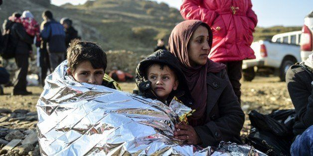 A Syrian family waits after arriving on the Greek island of Lesbos along with other migrants and refugees, on November 17, 20