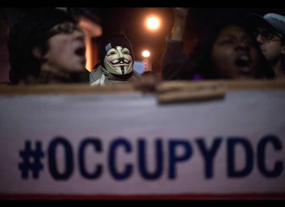 Protesters from Occupy DC march past the Washington Convention Center during a demonstration against the billionaire conserva
