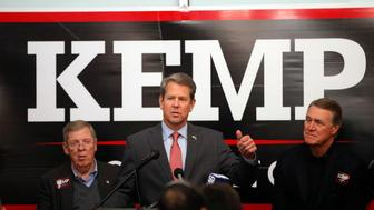 Georgia Republican gubernatorial candidate Brian Kemp, center, speaks to volunteers as Sen. Johnny Isakson (R-Ga), left, and Sen David Perdue (R-Ga) looks on during a stop at a campaign office Monday, Nov. 5, 2018, in Atlanta. Kemp is in a close race with Democrat Stacey Abrams. (AP Photo/John Bazemore)
