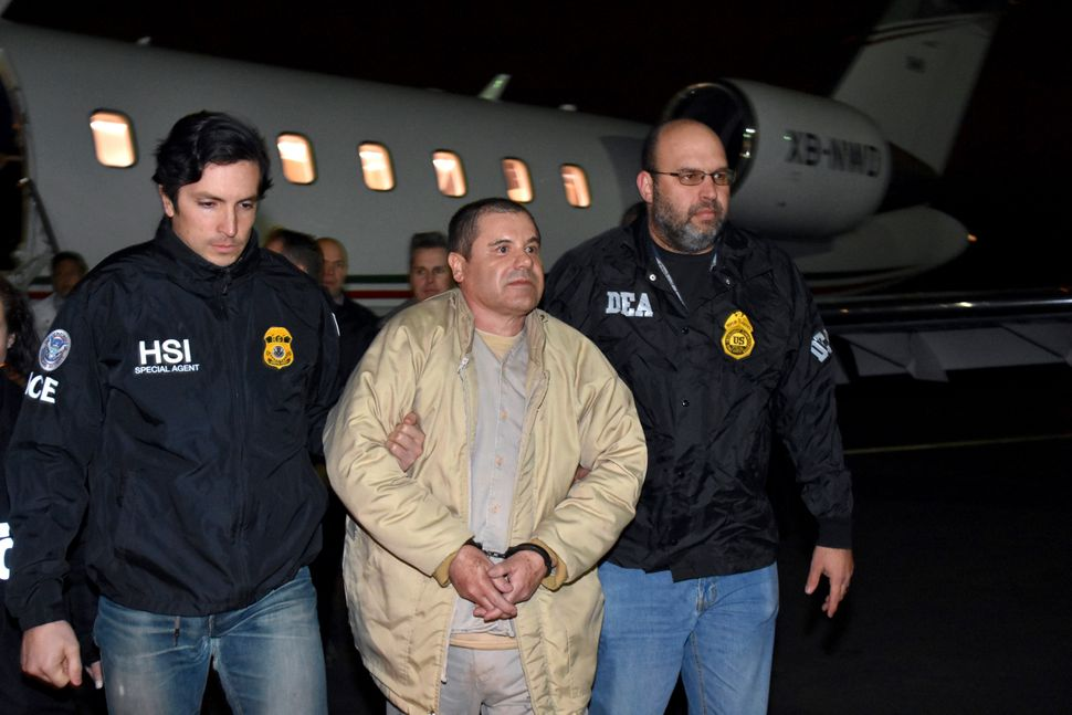 "Joaquin ""El Chapo"" Guzman is escorted from a plane to a waiting caravan of SUVs in New York's Long Island on Jan. 19, 2017."