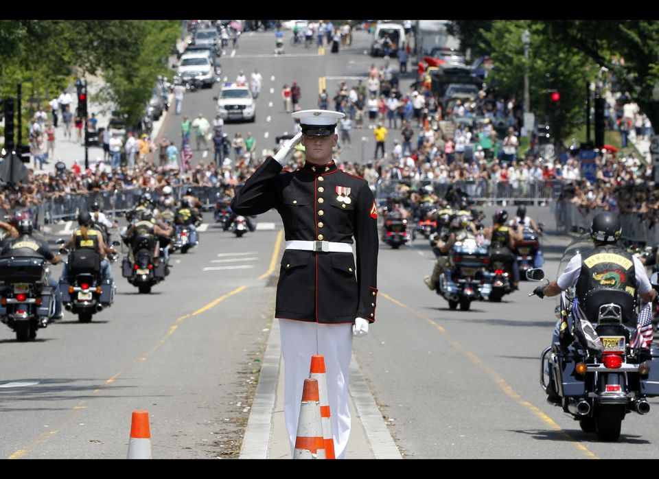 A Marine salutes as motorcycles drive past during the annual Rolling Thunder parade ahead of Memorial Day in Washington, Sund