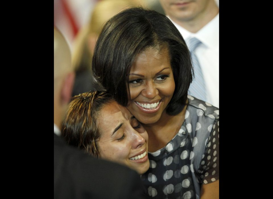 First lady Michelle Obama hugs a woman in the audience after Illinois Gov. Pat Quinn signed into law a measure allowing milit