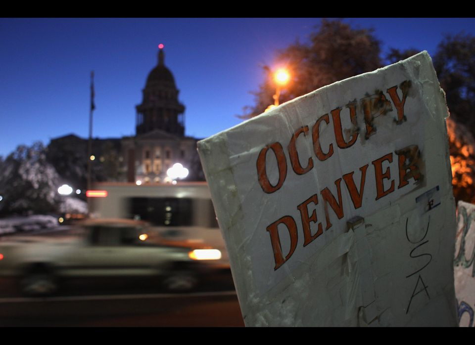 DENVER, CO - OCTOBER 27: Early morning traffic passes the Colorado state capitol building and the 'Occupy Denver' camp at daw
