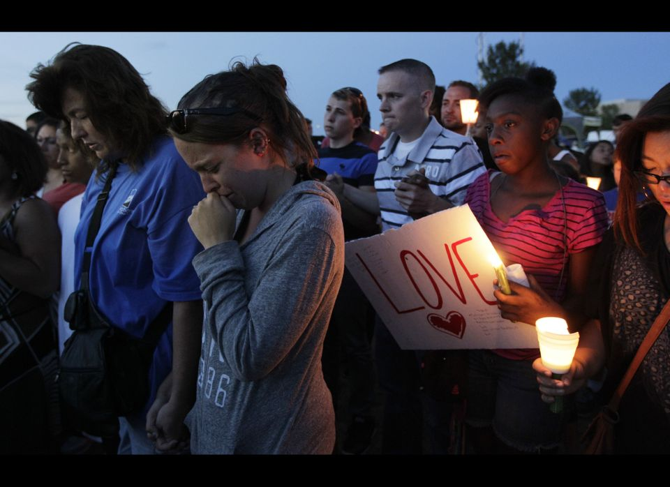 People attending a candle-light prayer gathering cry as they pray, Friday, July 20, 2012, in Aurora, Colo., across the street