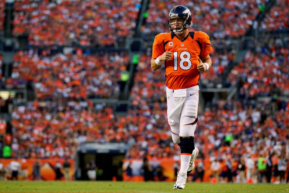 DENVER, CO - SEPTEMBER 9:  Quarterback Peyton Manning #18 of the Denver Broncos runs onto the field during a game against the