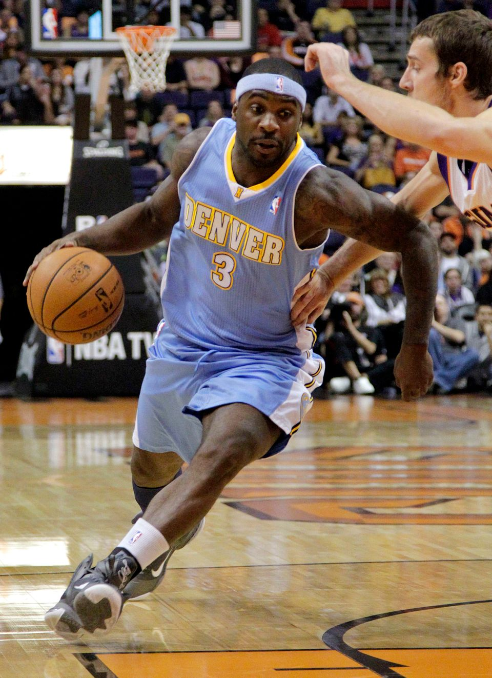 Denver Nuggets guard Ty Lawson (3) drives past Phoenix Suns guard Goran Dragic, of Slovenia, during the first half of a prese