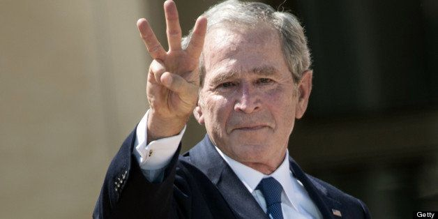 Former US President George W. Bush makes a 'W' with his fingers during a dedication ceremony at the George W. Bush Library an