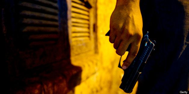 ASSIUT, EGYPT - JUNE 24: A young man in an alley holds a Beretta 9mm unliscenced pistol purchased illegally on June 24, 2013