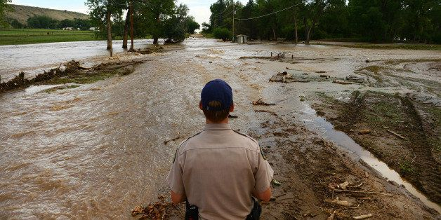 NORTH BOULDER, CO - SEPTEMBER 13: Colorado Parks and Wildlife officer Jason Duetsch looks at flooding across Oxford Road east