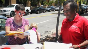 In this Thursday, June 28, 2018, photo, Rachelle Tracy signs a petition in downtown Little Rock, Ark., from canvasser Cynthia Ford in favor of putting a minimum wage hike proposal on the November ballot. Friday, July 6 is the deadline for initiative campaigns to submit signatures to qualify for the ballot. Ford also circulated petitions for the wage hike proposal, along with proposals to impose strict term limits and to legalize casinos. (AP Photo/Andrew DeMillo)