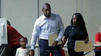 Florida Democratic gubernatorial candidate Andrew Gillum walks with his wife R. Jai Gillum, right, and his children Caroline and Jackson as he votes Tuesday, Nov. 6, 2018, in Tallahassee, Fla. Gillum is running against Republican opponent Ron DeSantis. (AP Photo/Chris O'Meara)