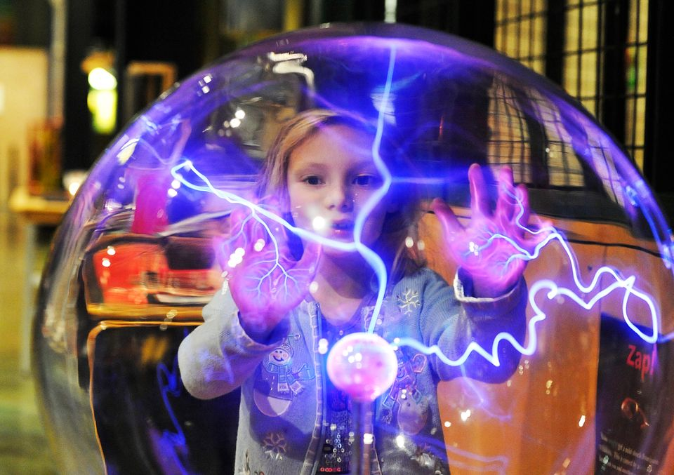 Nastia Karpov, 6, is fascinated as energy is attracted to her hands in a large plasma globe at the Michigan Science Center. T