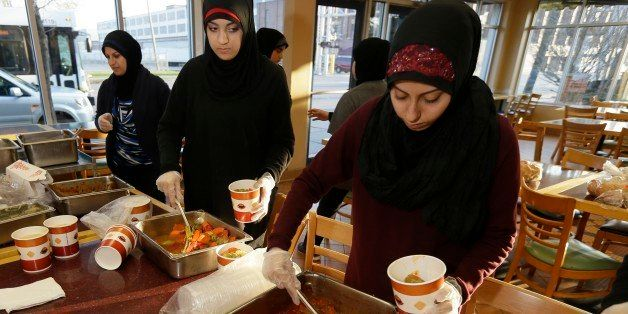 Volunteers Zahraa Debaja, center, and Zeinab Makki, right, prepare meals from food provided by the Yasmeen Bakery in Dearborn