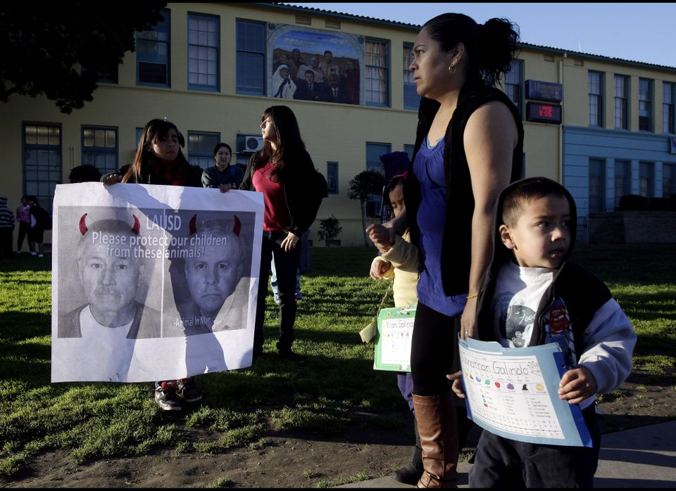 Nine-year-old Ashley Villatoro, left, holds a poster showing an image of former teacher Martin B. Springer as students arrive