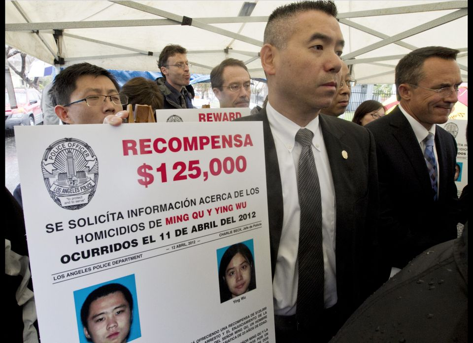 Los Angeles Police Department Officer Danny Chao, middle, holds a Spanish written poster offering a $125,000 reward offered b