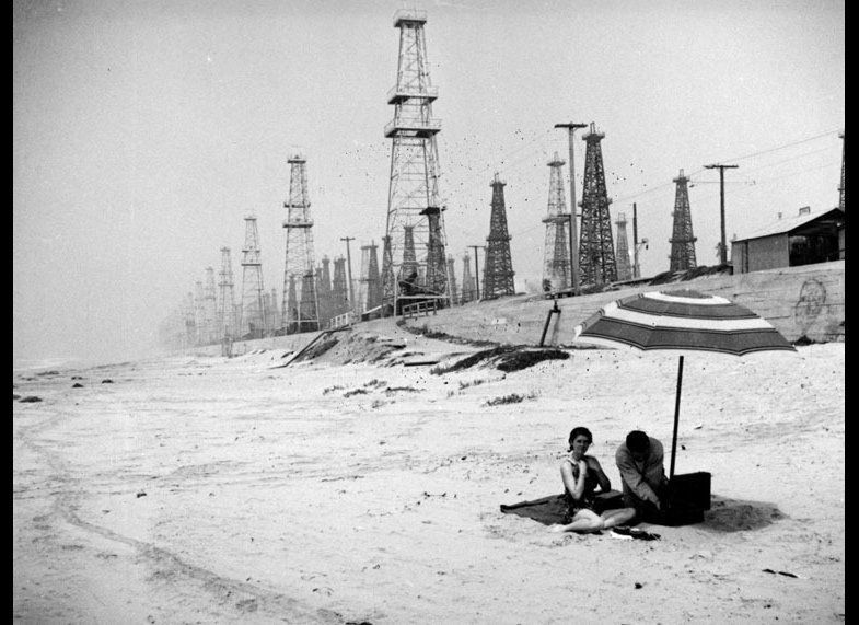 A couple of beach-goers surrounded by sunlight and oil derricks in Huntington Beach. Circa 1937.  (Herman J. Schultheis Colle