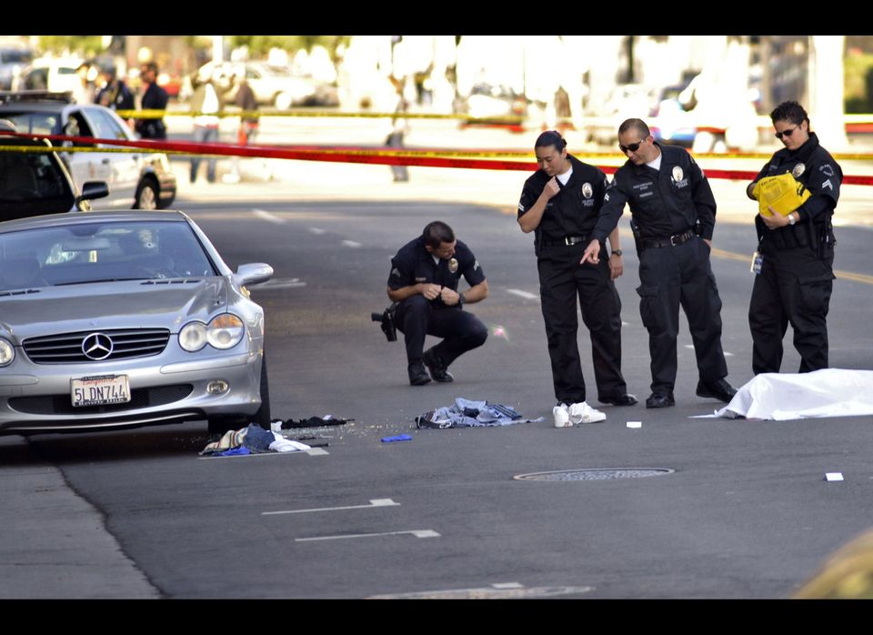 Investigators look over the scene of a fatal shooting, Friday, Dec. 9, 2011, in the Hollywood are of Los Angeles, Calif.
