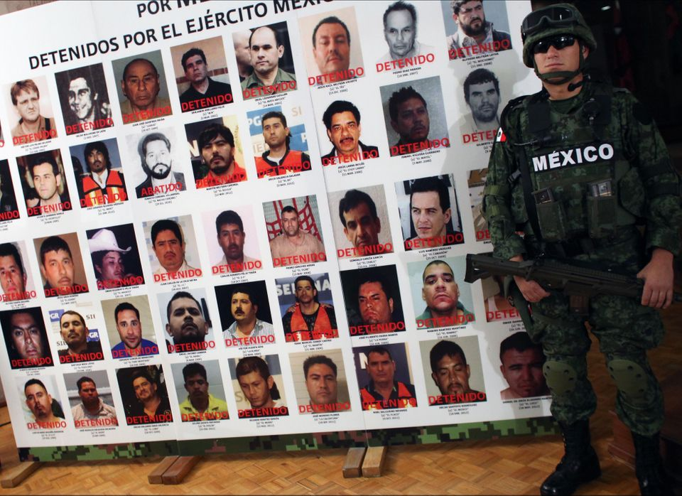 An army soldier stands next to a banner displaying mug shots of persons detained or killed by the Mexican Army during the med