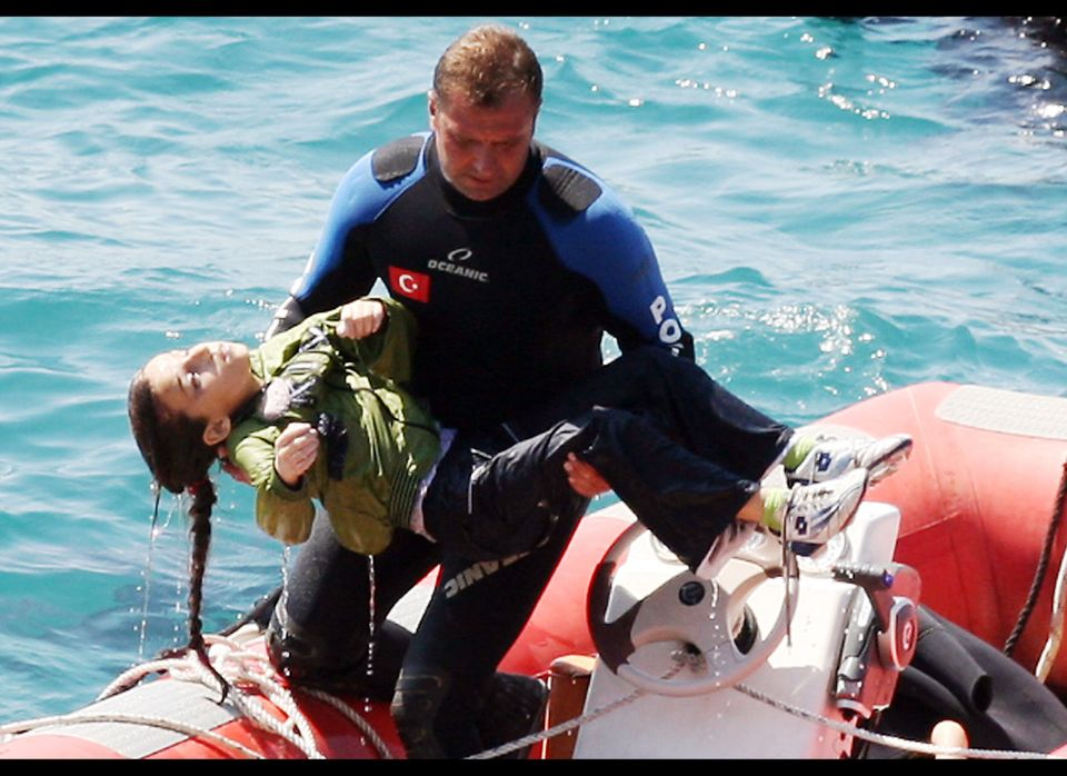 A diver carries a young girl, after a boat carrying illegal immigrants trying to reach Europe capsized in waters off western