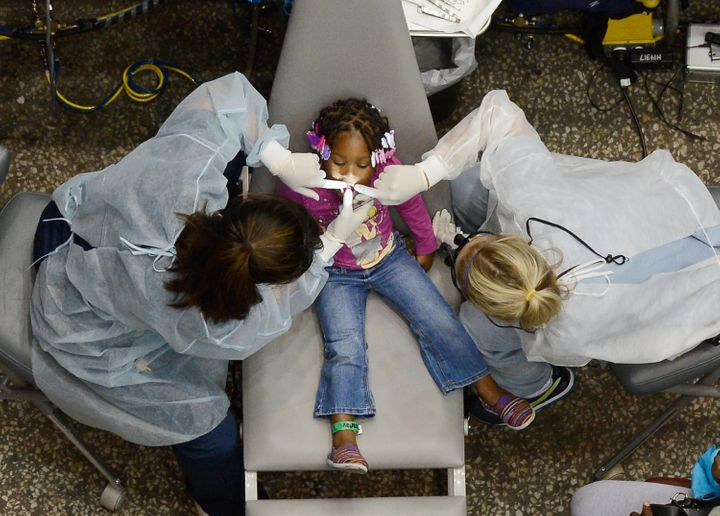 LOS ANGELES, CA - SEPTEMBER 27:  Kamora Cyprian, 2, gets her teeth cleaned as part of a free health care service at the Care