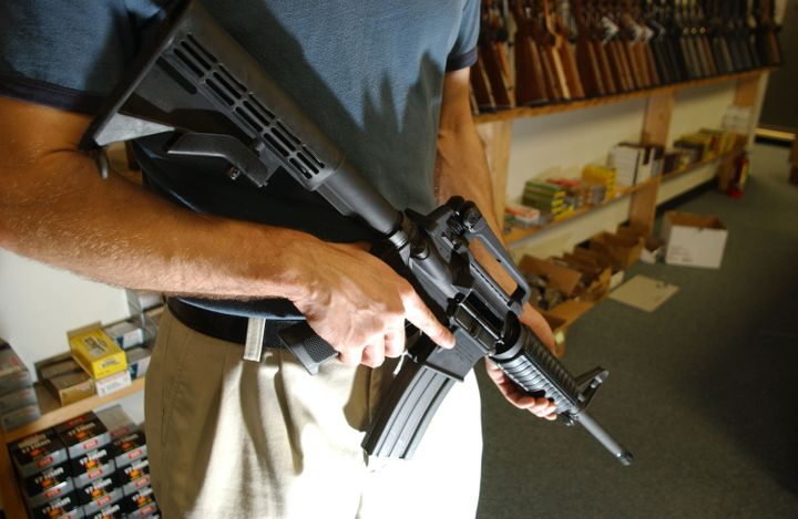 DENVER - SEPTEMBER 13:  The manager of Dave's Guns holds a Colt AR-15, now legal with a Bayonet Mount, Flash Suppressor and a