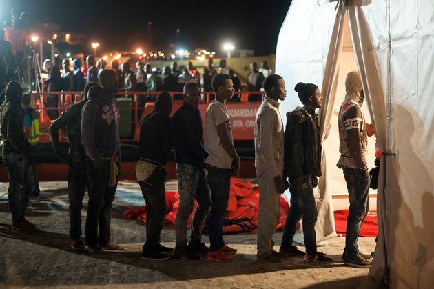 Des migrants attendent leur tour dans une tente de la Croix Rouge à Malaga en Espagne après...