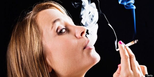 This beautiful young blonde looks round warily as she is caught smoking a joint of marijuana. Moody black background.