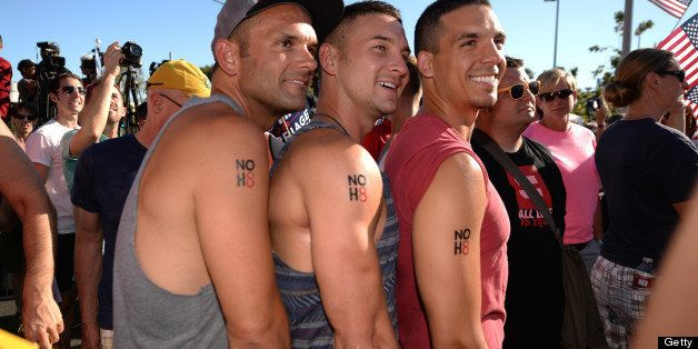 Same-sex marriage supporters Yale Scott (L), David Schulenberg (C) and Mark Martinez (R) show off their temporary tattoos rea